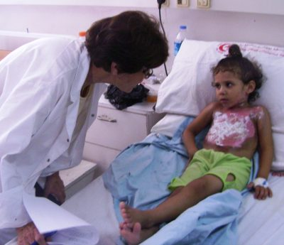 A photo of a doctor talking with her young patient at Ahli Arab Hospital