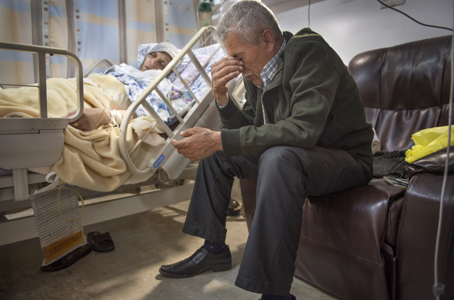 A photo of a man in grief while at the hospital sitting beside a dying patient.