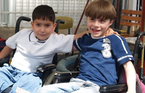 A photo of two boys with arms around each other in wheelchairs.