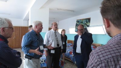 A photo of AFEDJ Trustees talking while viewing an dormitory facility.