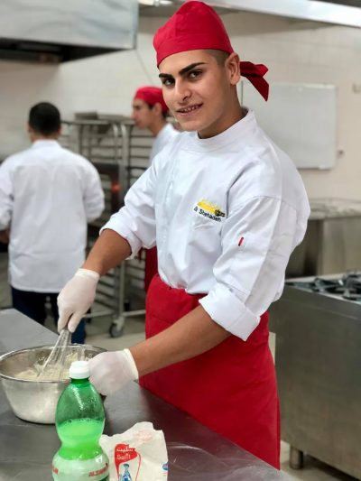 A young chef works in the kitchen of an AFEDJ Institution.