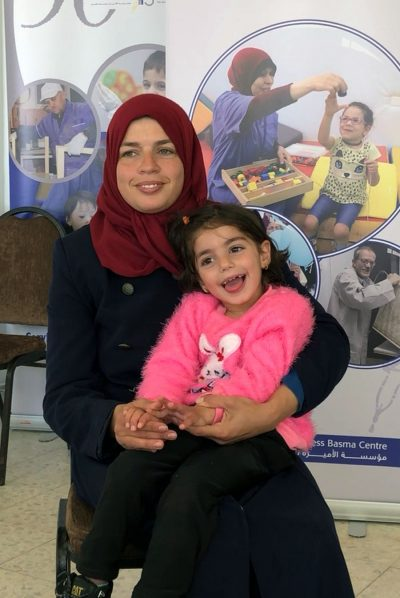 A photo of a smiling Basma mom with child.