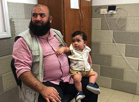 A father and his young son wait for the doctor, at Ahli Arab Hospital, Gaza City.
