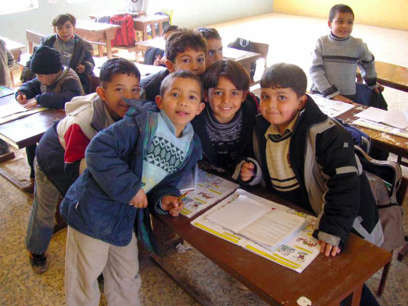 A photo of boys crowding around a school desk for picture. At Theodor Schneller School, Marka, Jordan