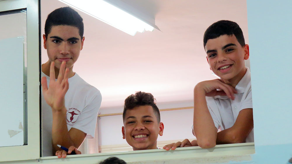 A photo of boys waving in a window at Arab Evangelical Episcopal School, Ramallah, West Bank