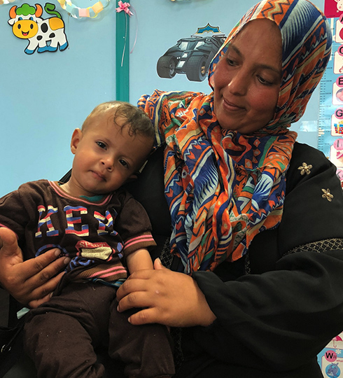 A mother and child waiting for treatment at Ahli Hospital.