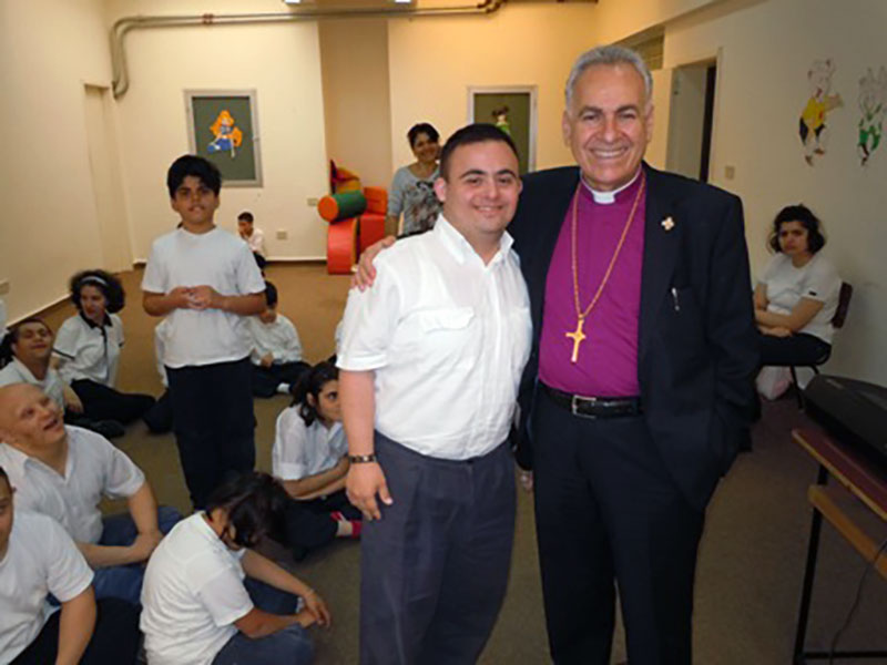 A photo of AFEDJ Trustee, The Most Rev. Suheil Dawani and a student at St. Luke's Center for Rehabilitation in Beirut, Lebanon