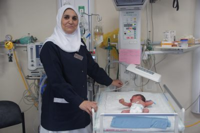 A photo of a nurse smiling at St. Luke's Hospital West Bank, Palestine.