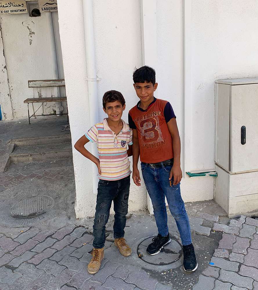 A photo of two boys standing outside Ahli Arab Hospital.