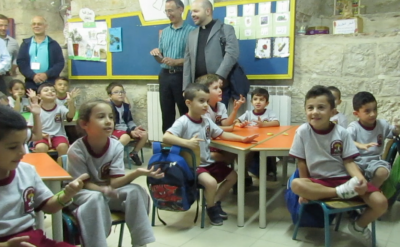 A photo of young elementary boys and girls in classroom at Palestinian school, St. George's.