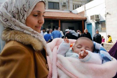 A photo of a mother and infant waiting for treatment at the Ahli Arab Hospital Free Clinic in Gaza.