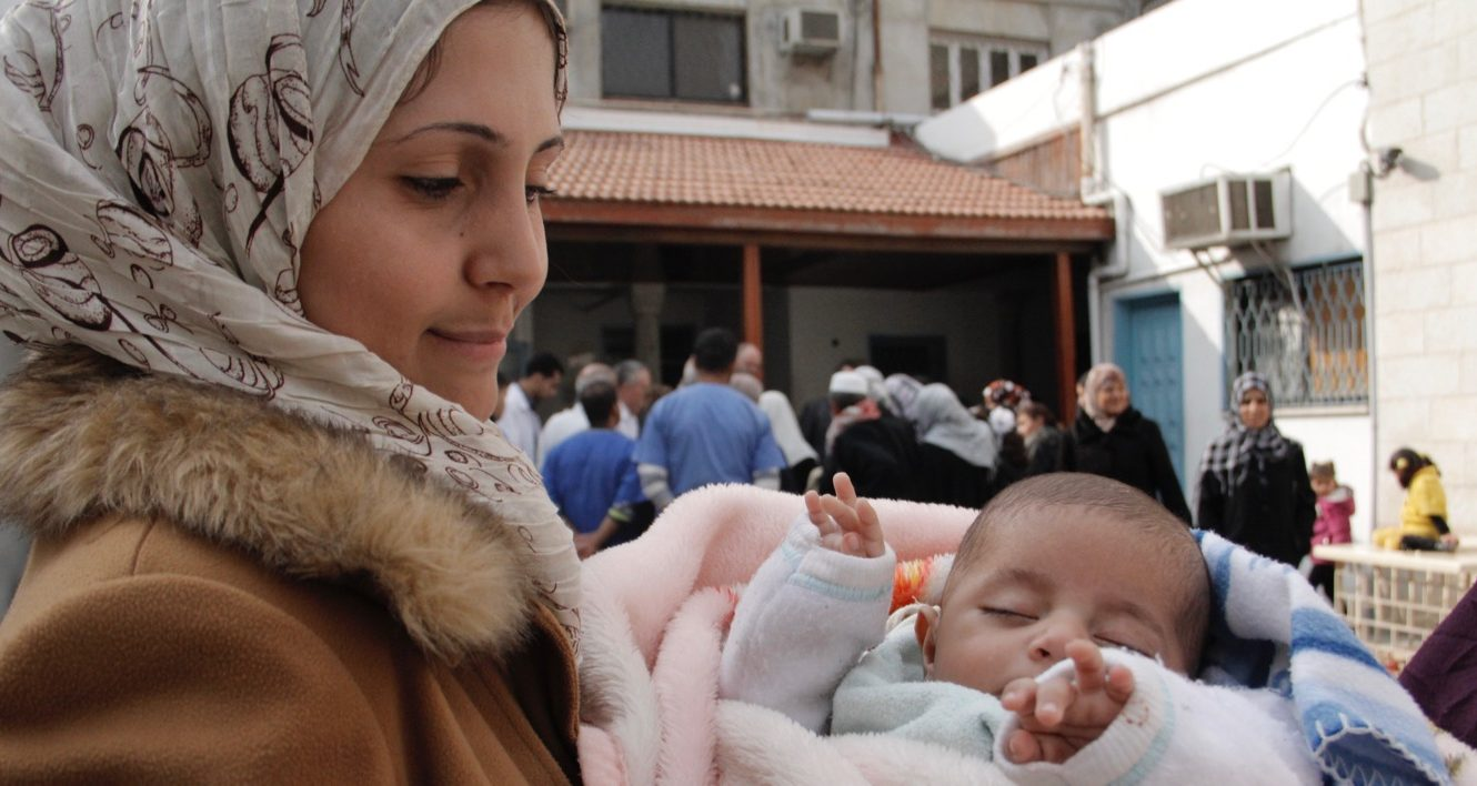 A mother and her infant await treatment outside of the Ahli Hospital Free Community Clinic in Gaza