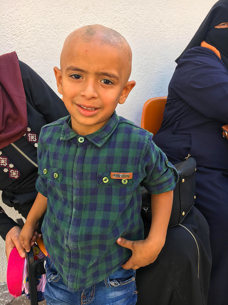 A photo of a boy in a plaid shirt outside Ahli Arab Hospital