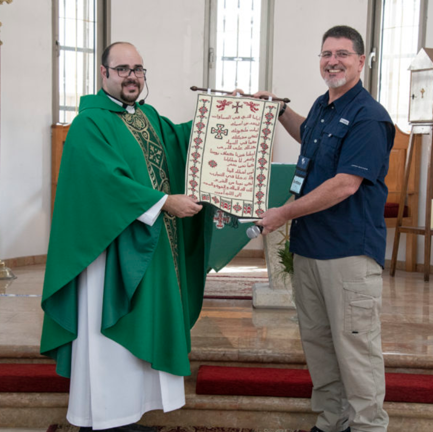 Father Jamil Monir Khadir presents Ben Trawick a needlepoint of the Lord's Prayer made by the ladies of the church at the Church of the Good Shepherd in Rafidia, Palestine.