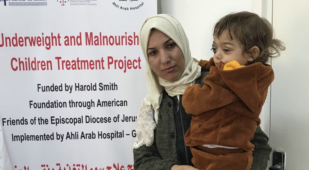 A mother and child wait for treatment at Ahli Arab Hospital in Gaza