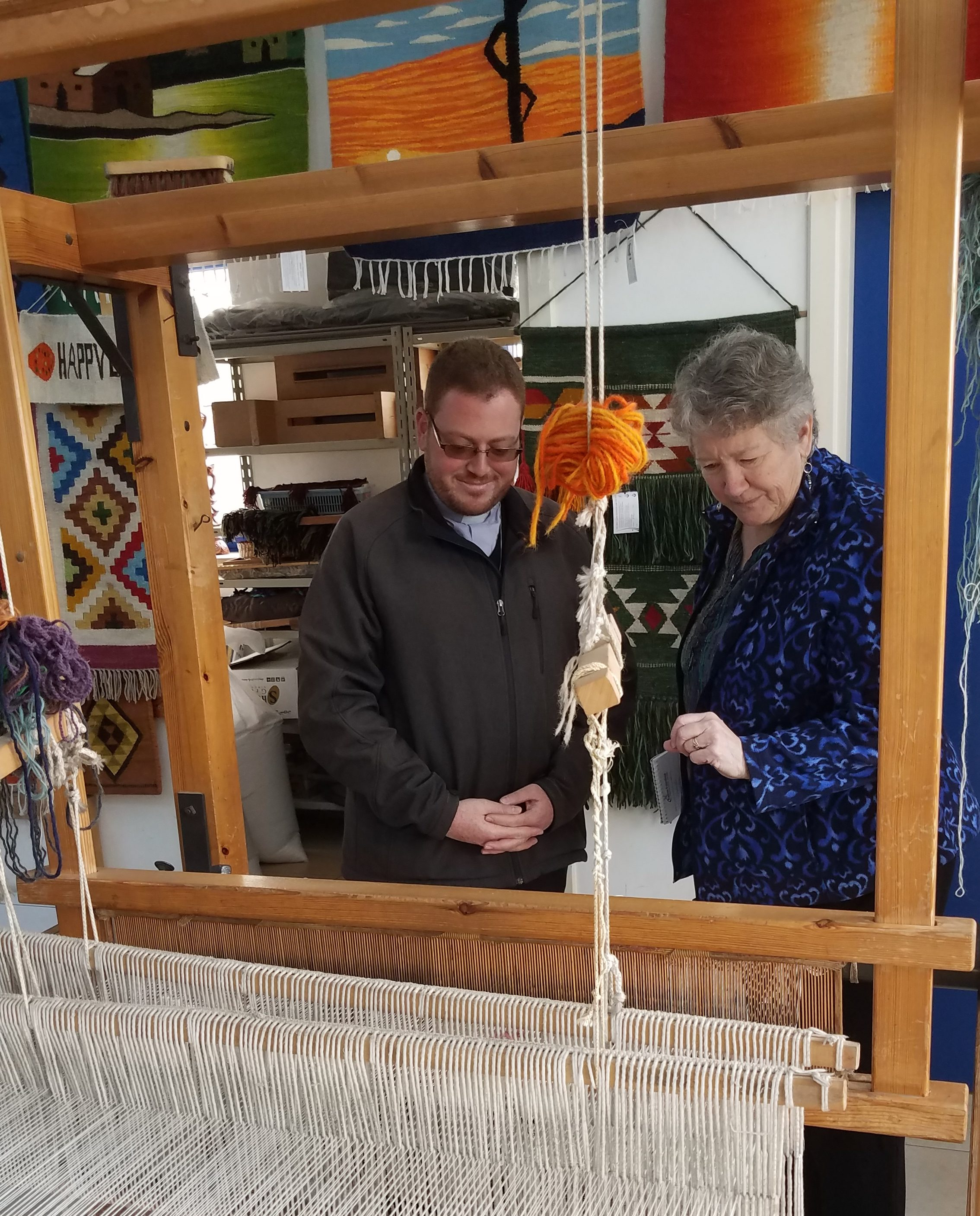 Fr. Wadie Far of HLID shows Doni Heyn-Lamb the looms used by vocational students at Holy Land Institute for the Deaf
