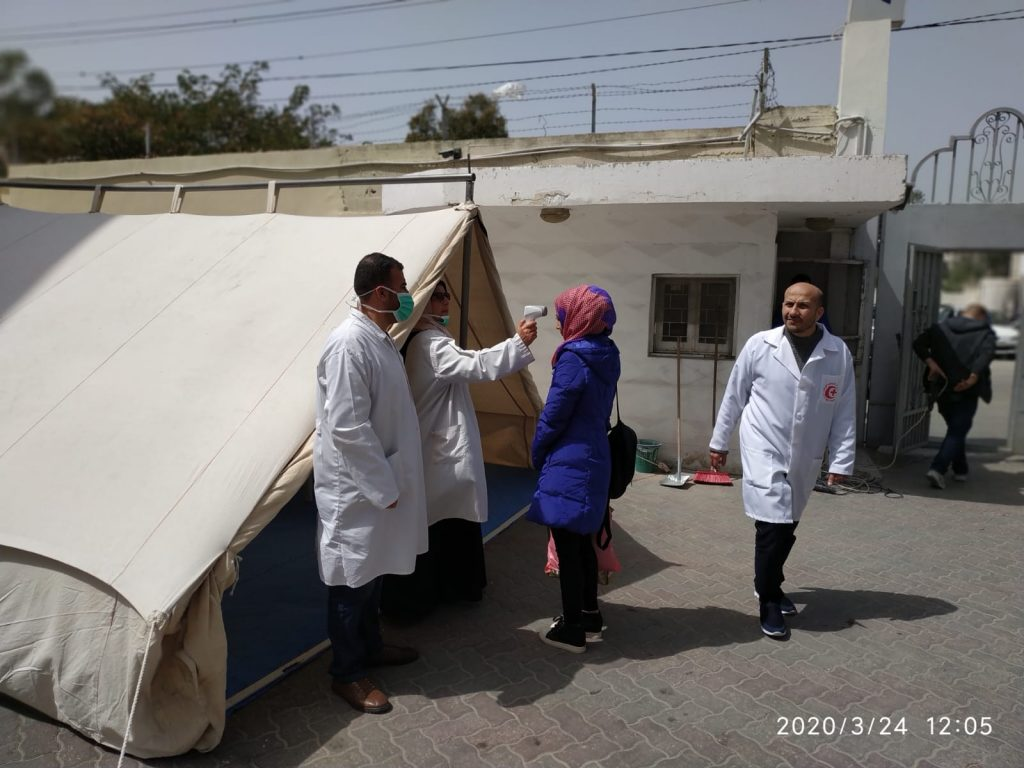 A patient is checked for fever at a triage tent at Ahli Arab Hosptial in Gaza City